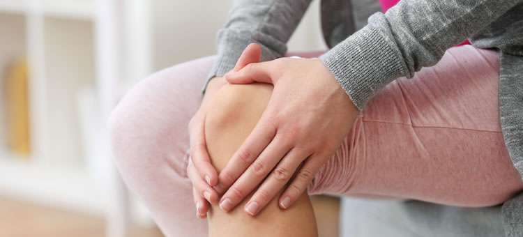 woman holding sore knee